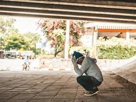 morador de rua sentado embaixo da ponte com as duas mãos segurando a cabeça foto