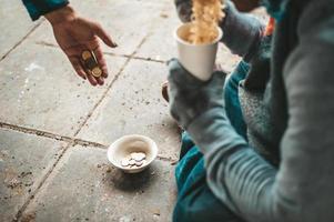 mendigo sentado sob uma ponte com uma xícara de dinheiro e macarrão