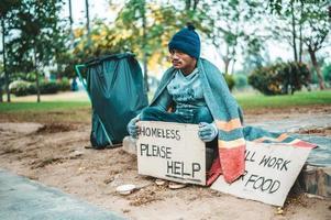 mendigo embrulhado em pano na rua aceitando dinheiro