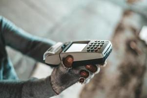 mendigo sentado sob um viaduto com uma máquina de passar cartão de crédito