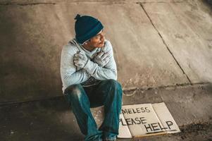 mendigo sentado embaixo do viaduto com uma placa de ajuda foto