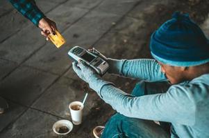 mendigos sentados sob a ponte com uma máquina de passar cartão de crédito