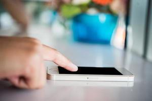 close-up das mãos de uma mulher usando o celular com a tela de cópia em branco foto