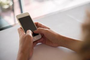 close-up da mão de uma mulher usando um telefone celular foto