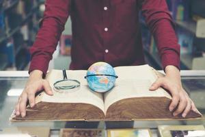 jovem estudante segurando um modelo terrestre na mão foto