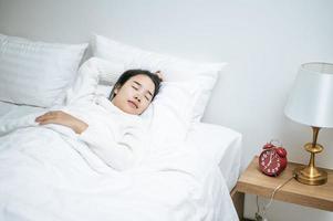 jovem de camisa branca acabando de acordar na cama foto