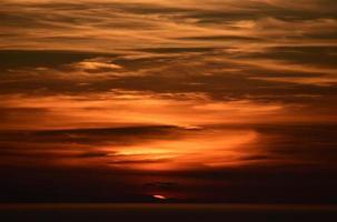 céu nublado laranja colorido ao pôr do sol foto