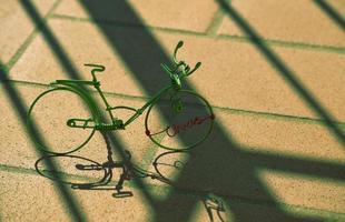 bicicleta miniatura de arame verde com sombras no pavimento de concreto