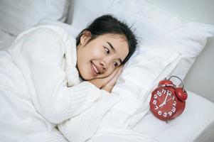 uma mulher vestindo uma camisa branca deitada em sua cama com um despertador foto