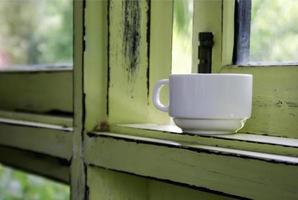 xícara de café no parapeito da janela foto