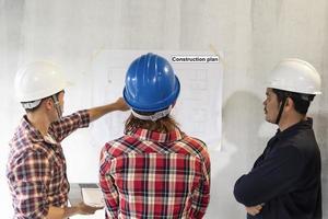 engenheiros asiáticos com capacetes colocados foto