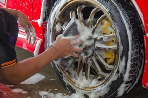 lavando os pneus de um carro vermelho