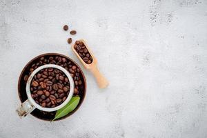 grãos de café torrados com colheres configuradas em fundo branco de concreto foto