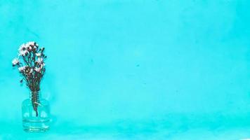 flores em um vaso sobre fundo azul foto