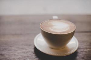 café latte art vintage com formato de coração na mesa de madeira