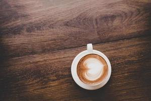 vista superior do café latte art vintage com formato de coração na mesa de madeira