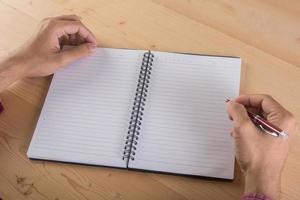 close-up da mão do empresário escrevendo com o caderno foto
