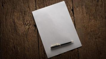 folha de papel em branco e caneta em uma mesa de madeira foto