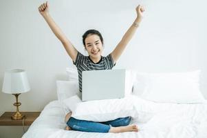 uma jovem brincando em seu laptop na cama foto