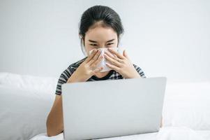 mulher brincando no laptop segurando um lenço de papel para limpar o nariz foto