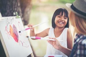 mãe e filha fazendo um desenho juntas no parque