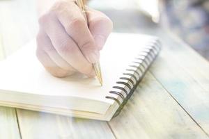mão escrevendo em um caderno foto