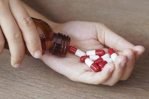 segurando cápsulas vermelhas e brancas
