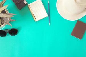 passaporte, chapéu e caderno sobre fundo verde