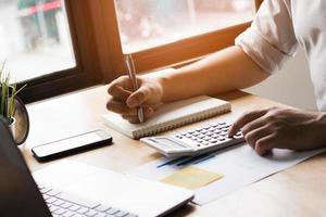 pessoa escrevendo em um diário e usando calculadora foto