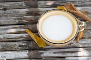 café na mesa de madeira com folhas de outono