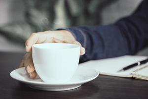 mão segurando uma xícara de café foto