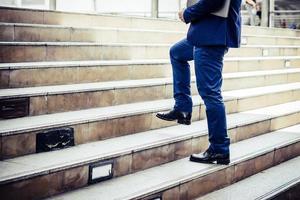 close-up do jovem empresário subindo as escadas fora do escritório foto