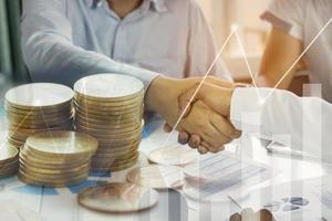 duas pessoas apertando as mãos com sobreposição de dinheiro