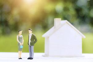 duas pessoas estatuetas com uma casa modelo foto