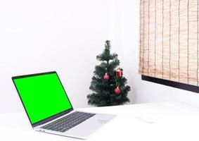 laptop na mesa com modelo de árvore de natal