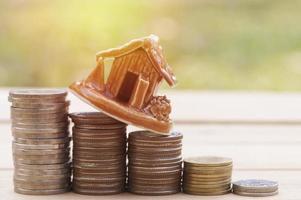 pequena casa modelo com pilhas de moedas foto