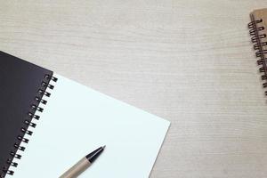 caderno e caneta em uma mesa foto