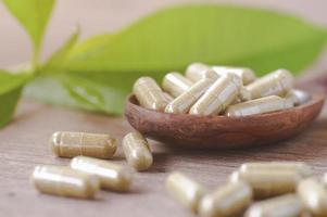 cápsulas de comprimidos marrons em uma mesa de madeira foto
