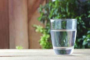 copo de água potável no fundo de madeira foto