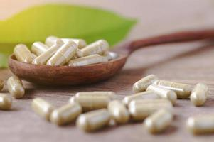 cápsulas de ervas medicinais no carretel de madeira com folhas na mesa de madeira foto