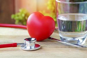 estetoscópio, coração vermelho e água potável foto
