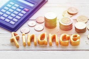 letras financeiras com moedas e uma calculadora