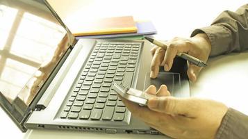 profissional trabalhando em laptop e telefone