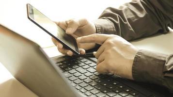 profissional usando um telefone e um laptop