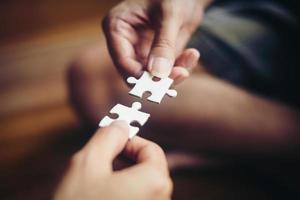 mãos segurando quebra-cabeças foto