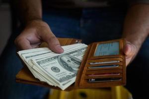 mãos tirando dólares da carteira foto