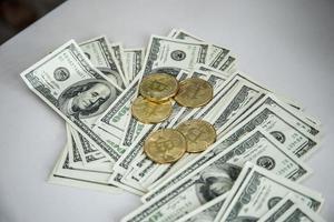 moedas de ouro de bitcoin em notas de dólar foto
