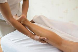 close-up de massoterapeuta massageando perna feminina em salão de spa foto