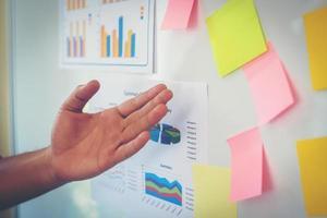 close-up da mão apresentando o gráfico de negócios no quadro branco foto