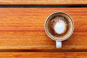 vista superior da xícara de café no fundo da mesa de madeira foto
